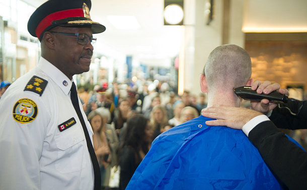 A man in TPS uniform watches as a man is shaved with clippers