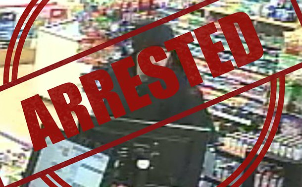 "A security camera image of a man in a store with the word ""arrested"" over top of the image"