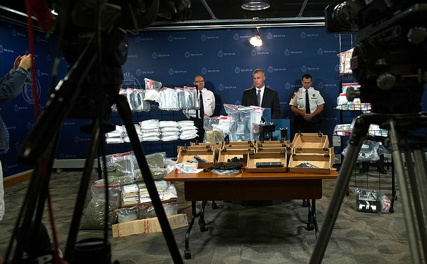 A man at a podium with video cameras pointed at him and drugs, weapons and money in evidence containers on tables and racks beside him