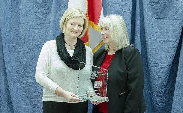 Two women, one holds a glass award