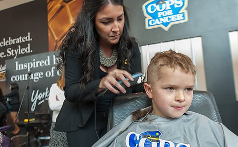 A boy has his head shaved by a woman