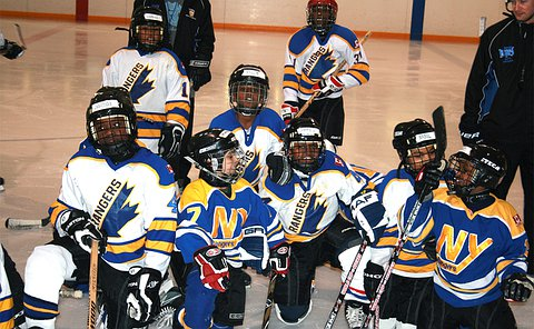 A group of boys in hockey uniform, helmets and skates take a knew of the ice