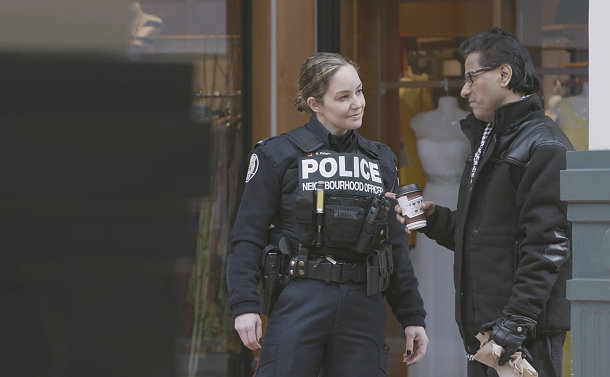 A woman in TPS uniform speaking to a man