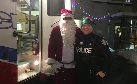 A man in a Santa costume with a man in TPS uniform