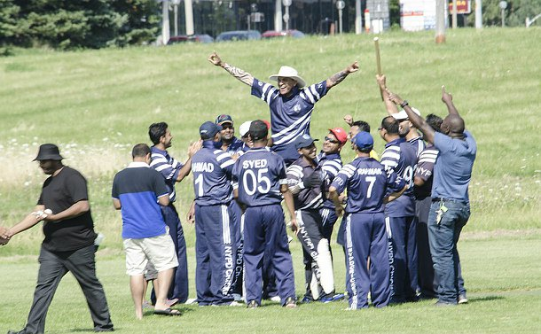 A group of men in cricket uniforms crowd around a player who jumps in the air