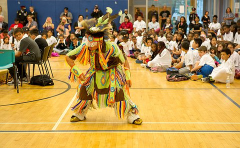 A boy in aboriginal clothing dancing