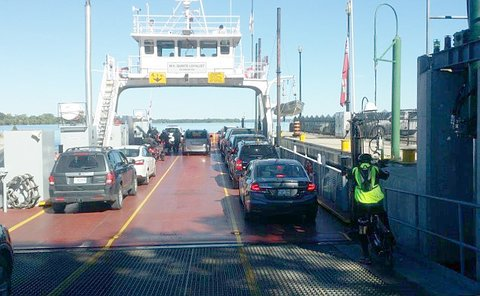 A man on a elliptical bicycle with cars loading on a ferry