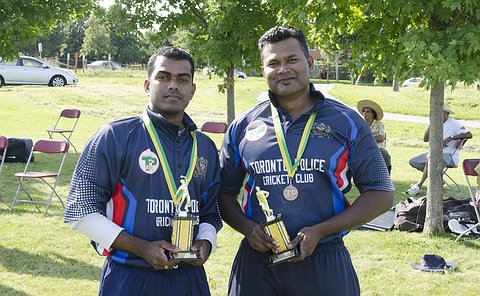 Two men in cricket uniforms hold trophies