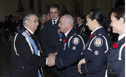 Two men in uniform shake hands as others look on