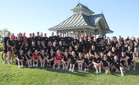 A large group of men and women in black T-shirts on grass near a gazebo