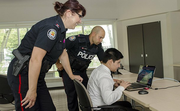two officers lean over a boys shoulder as he sits on a desk looking at a laptop, everyone is smiling
