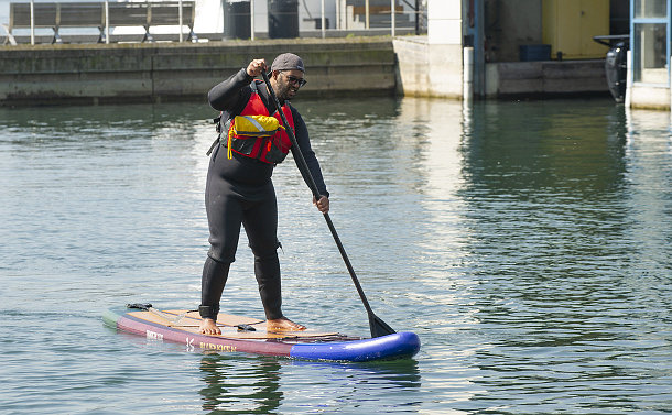 A man on a paddleboard on the water