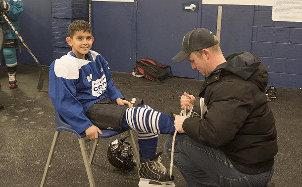 A man kneels to tie a boy's hockey skates
