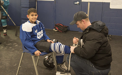 A man kneels to tie a boy's hockey skates