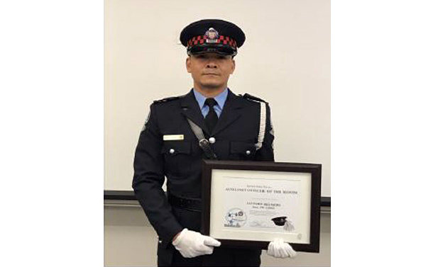 Man wearing a uniform of an auxiliary police officer holds an award plaque