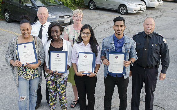 Three teenage girls, one teenage boy holding certificates standing with a woman and two men in TPS uniform