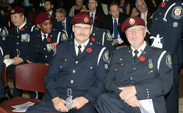 Two men sitting in the audience among many other, wearing police military veteran uniforms.