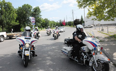 A group of people in TPS uniform on TPS motorcycles