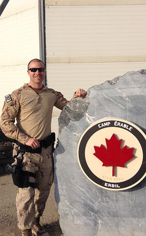 A man beside a Camp Canada sign on a rock