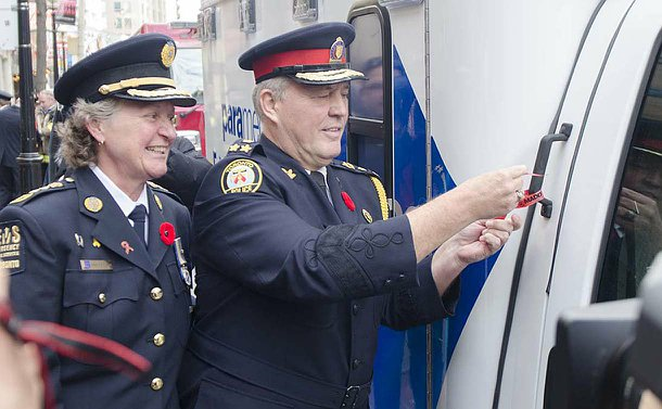 A man and woman in uniform, man tying red ribbon to an ambulance