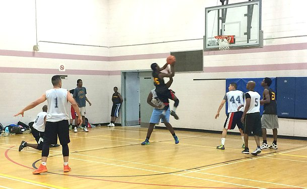 A group of people play basketball, one person jumps towards the basket holding a ball