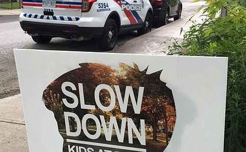 A police SUV parked behind another SUV near a sign that reads: Slow Down, Kids at Play