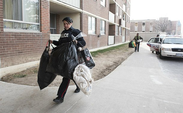 A woman in TPS uniform walks with bags