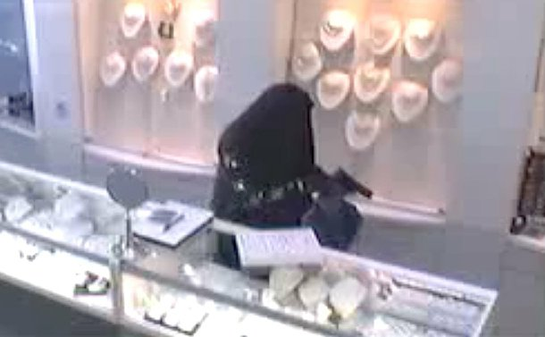 A man in a black head covering and robe behind a jewellery counter with a  gun