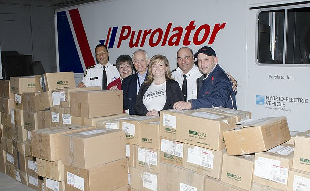 A group of men and women, two in TPS uniform, another in a Purolator uniform behind boxes stacked chest high with a courier truck in the background