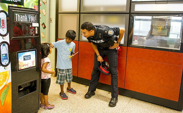An officer in uniform leaning down to speak to a boy and girl