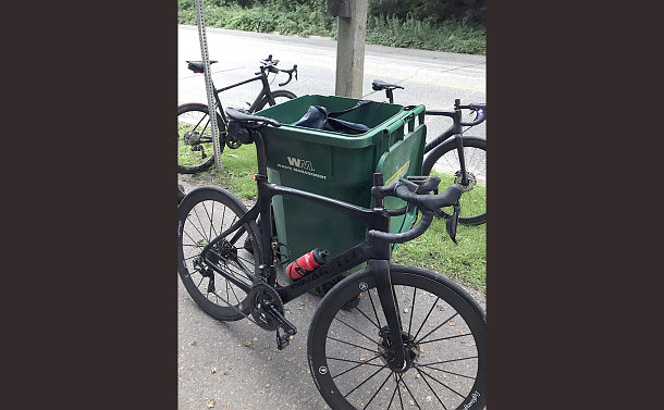 Several bicycles parked around a large green waste bin