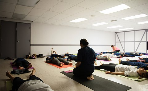 A woman kneels in a room with women and girls laying on mats