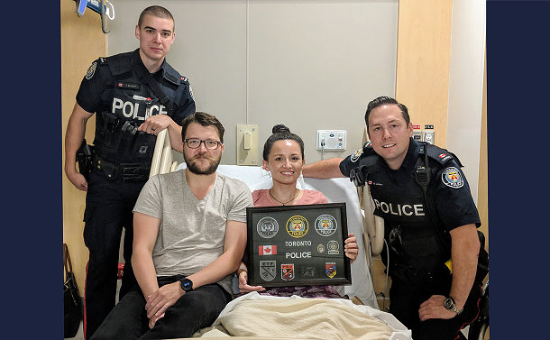 Two men in TPS uniform with a man and woman in a hospital bed
