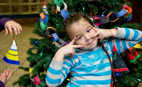 A young girl in a blue striped shirt posing in front of a Christmas tree.