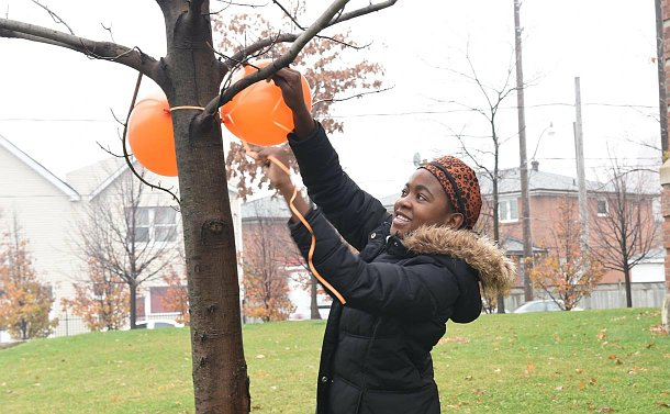 A girl ties a ballon to a tree