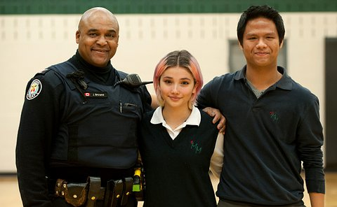 An officer standing next to two teenage students - a girl and a boy - both of whom are wearing school uniforms.