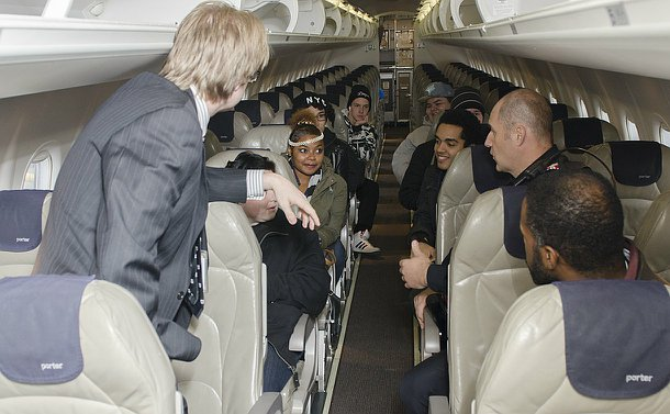 A group sit inside a commercial airplane