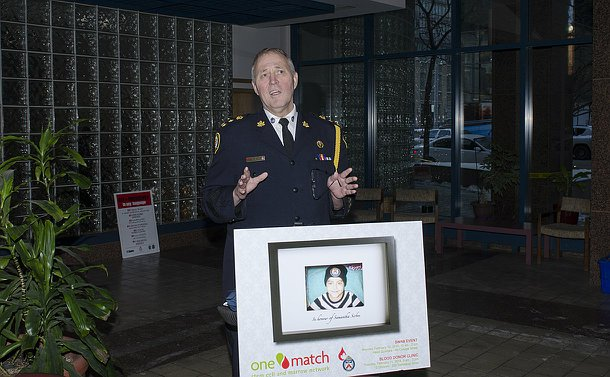 A man in Toronto Police uniform speaks in front of a sign advertising the clinic