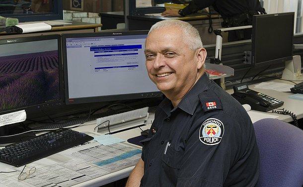 A man in TPS uniform sits near a computer