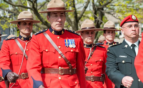 Officers in RCMP uniforms marching.