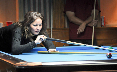 A woman playing pool