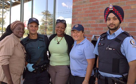 A group of people including one man wearing a TPS uniform and one man wearing an TPS auxiliary uniform