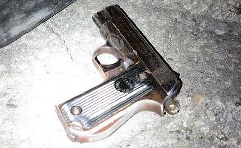 A silver gun on a sidewalk