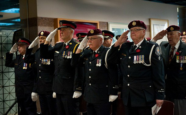 A row of men in uniform saluting