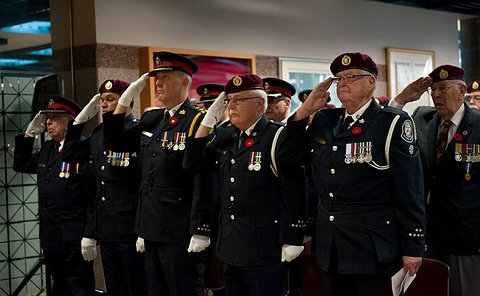 A row of men in uniform saluting