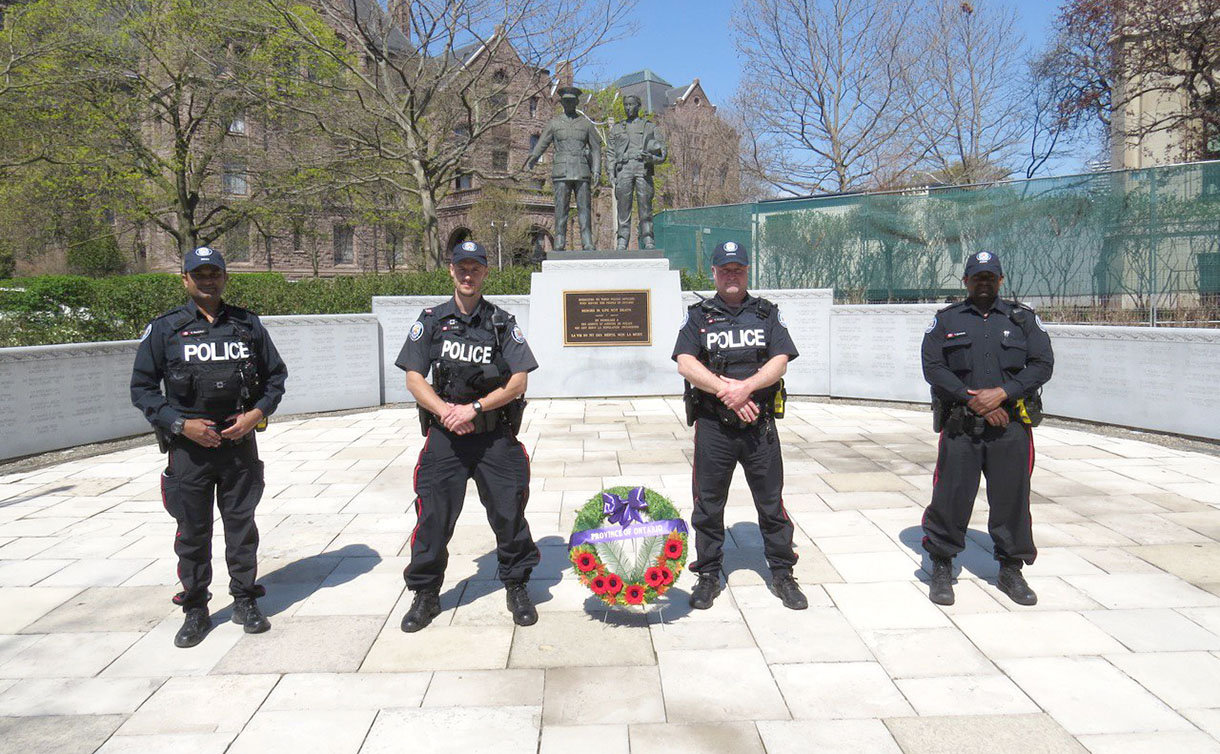 Four men in TPS uniform with a wreath