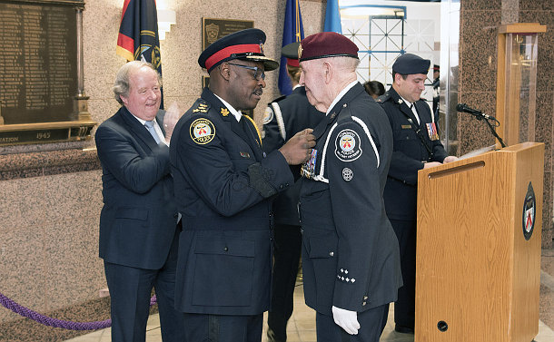 Two men in police uniforms, one pinning a medal to the other's chest, while another man in a suit claps