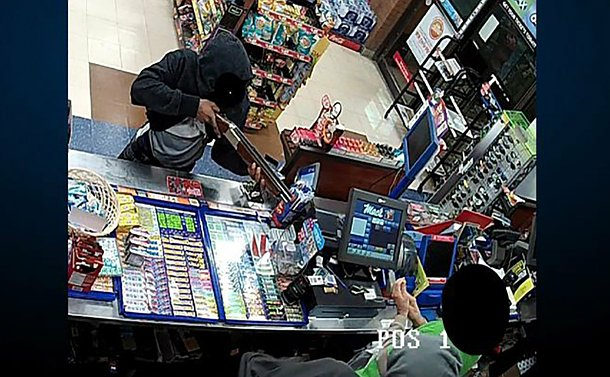 A man pointing a sawed off rifle at a man behind a counter