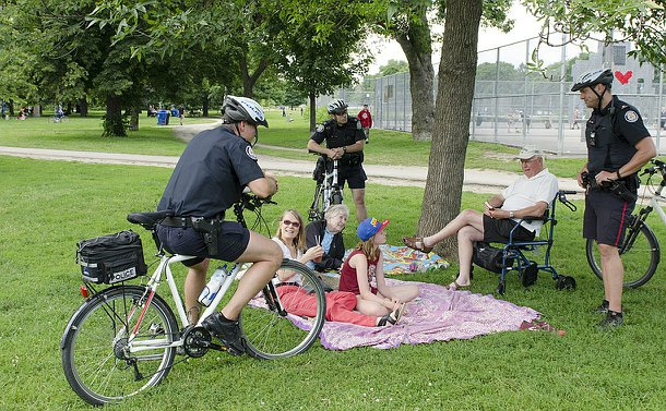 Two women and a girl lay on a blanket, one man is seated and three men in TPS uniform and bicycles talk to them