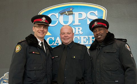 "Three uniformed TPS members standing in front a poser that reads ""cops for cancer"""